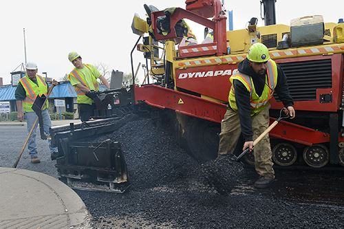 A picture of the Morgantown Public Works Department personnel paving a road.