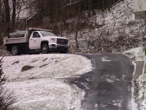 A picture of a Morgantown Public Works snow plow spreading salt on a tertiary road.