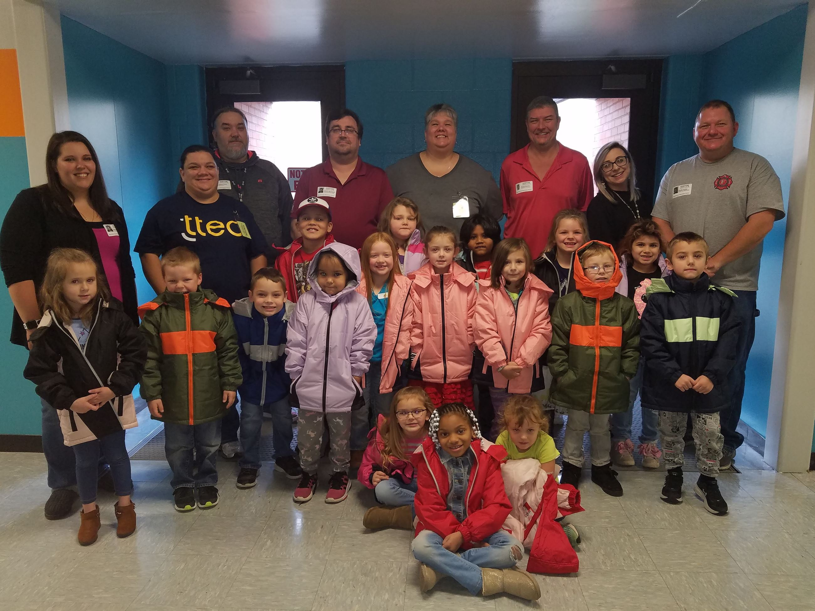 A photo of Local 313 Firefighters with children that received a coat from Operation Warm