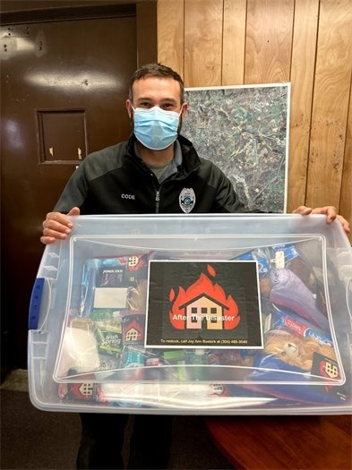 Image of Code Enforcement officer Drew Cantis holding the kit tote.